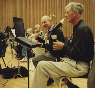 3. The first in a series of pictures illustrating the use of technology to magnify music. This shows a recorder ensemble of four players. One of them faces a music stand with a computer monitor mounted on it. Caption reads