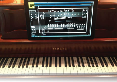 5. Large-screen tablet laptop on the music rack of a piano and displaying magnified music as white notes on a black background. Caption reads