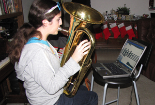 4. photo of a girl playing the Euphonium in a living room, in front of a monitor showing enlarged music. Caption reads